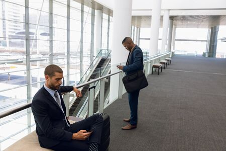 Side view of a young Caucasian businessman with a suitcase sitting on a bench using his smartphone in a modern corridor while a young African American businessman stands looking at his phone in the background. Modern corporate start up new business concept with entrepreneur working hard
