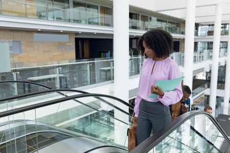 Front view of a young African American businesswoman holding a file and a handbag at the top of an escalator in a modern building. In the background incidental people are visible behind her. Modern corporate start up new business concept with entrepreneur working hard