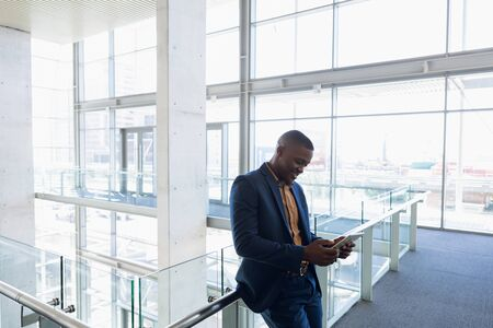 Side view of young African American businessman using a tablet computer standing on a mezzanine in the atrium of bright modern business building. Modern corporate start up new business concept with entrepreneur working hard Archivio Fotografico