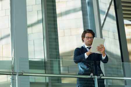 Low angle view of businessman leaning on railing and using digital tablet in corridor at modern office. Modern corporate start up new business concept with entrepreneur working hard Imagens