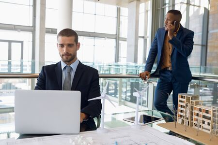 Front view of young Caucasian businessman using laptop sitting at a desk in an architectural office. A young African American businessman is standing using smartphone in the background. Modern corporate start up new business concept with entrepreneur working hard