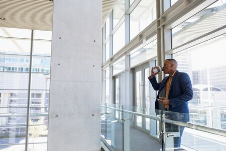 Side view of young African American businessman drinking a takeaway coffee standing on a mezzanine in a bright modern business building. Modern corporate start up new business concept with entrepreneur working hard