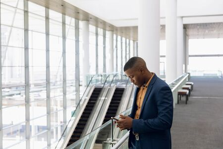 Side view of young African American businessman using smartphone standing in the glass walled lobby of a modern business building. Modern corporate start up new business concept with entrepreneur working hard Фото со стока