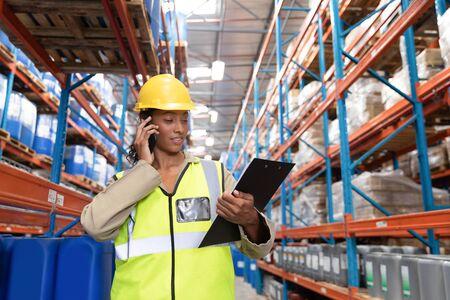 Widok z przodu pracownica patrząc na schowek podczas rozmowy na telefon komórkowy w magazynie. Jest to magazyn transportu i dystrybucji towarów. Koncepcja pracowników przemysłowych i przemysłowych