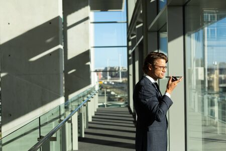 Side view of businessman talking on mobile phone while looking through window in corridor at modern office. Modern corporate start up new business concept with entrepreneur working hard