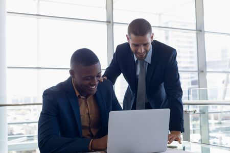 Front view of young African American businessman sitting in front of the window in an office looking at a laptop with a young Caucasian businessman standing beside him with hand on his shoulder. They are both smiling. Modern corporate start up new business concept with entrepreneur working hard Banco de Imagens