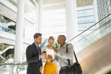 Front view of a young African American businessman holding tablet computer and showing it to a young Caucasian businessman and businesswoman while they talk in the lobby of a modern building. Modern corporate start up new business concept with entrepreneur working hard