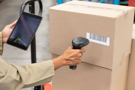 Close-up of female worker scanning package with barcode scanner while using digital tablet in warehouse. This is a freight transportation and distribution warehouse. Industrial and industrial workers concept
