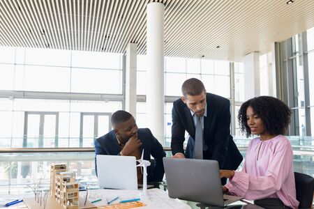 Front view of a young Caucasian businessman standing at a desk talking with a young African American businessman and businesswoman sitting using laptops working together in a modern office. Modern corporate start up new business concept with entrepreneur working hard