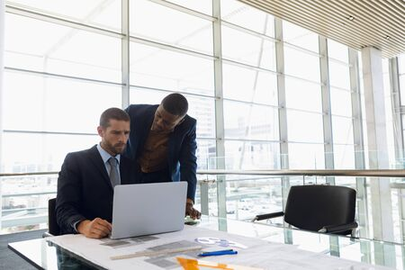 Front view of young Caucasian businessman sitting in front of the window in an office looking at a laptop with a young African American businessman standing beside him talking. Modern corporate start up new business concept with entrepreneur working hard Banco de Imagens