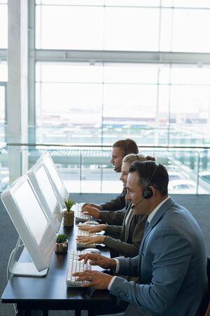 Business people with headset working on computer at desk in office. Modern corporate start up new business concept with entrepreneur working hard Stockfoto