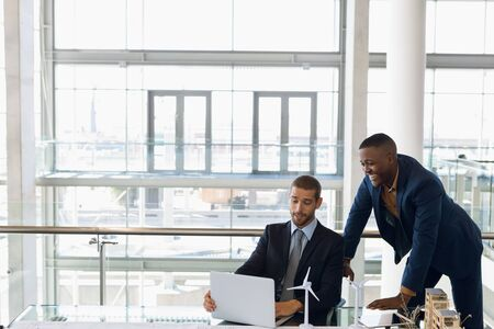 Front view of young Caucasian businessman using laptop sitting at a desk in a modern office working with a smiling young African American businessman standing behind him. Modern corporate start up new business concept with entrepreneur working hard