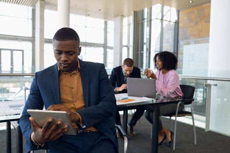 Front view cloe up of young African American businessman sitting using tablet computer in an office. A Caucasian businessman and an African American businesswoman work sitting at a desk in the background. Modern corporate start up new business concept with entrepreneur working hard