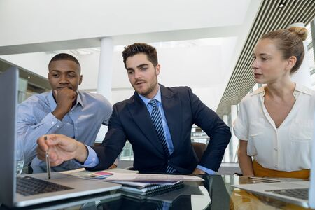 Front view of young African American businessman and a young Caucasian businesswoman and businessman working together sitting at desk in a modern office. Modern corporate start up new business concept with entrepreneur working hard