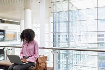 Front view of young African American businesswoman using laptop sitting in the lobby of a modern office building. Modern corporate start up new business concept with entrepreneur working hard Banco de Imagens