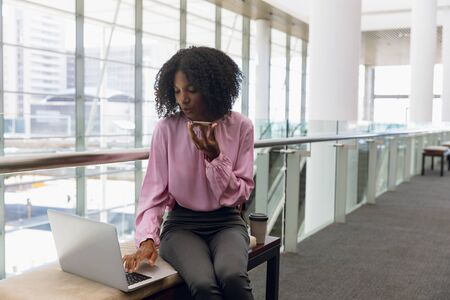 Front view of young African American businesswoman working on a laptop and talking on her phone sitting in the lobby of a modern office. Modern corporate start up new business concept with entrepreneur working hard Фото со стока