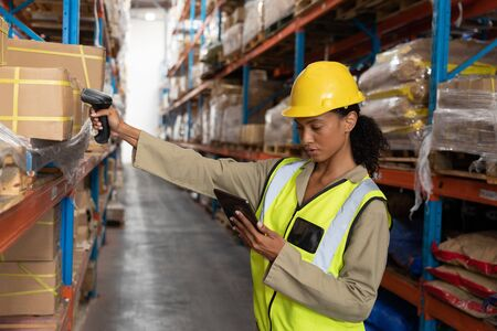 Side view of female worker scanning package with barcode scanner while using digital tablet in warehouse. This is a freight transportation and distribution warehouse. Industrial and industrial workers concept