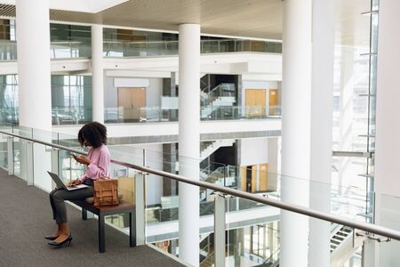 Full length side view of young African American businesswoman using smartphone and laptop sitting in the lobby of a modern office building. Modern corporate start up new business concept with entrepreneur working hard