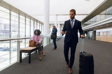 Full length front view of a young Caucasian businessman looking at smartphone while he walks wheeling a suitcase in a modern corridor. In the background an African American businesswoman is sitting on a bench and an African American businessman is talking on his phone. Modern corporate start up new business concept with entrepreneur working hard