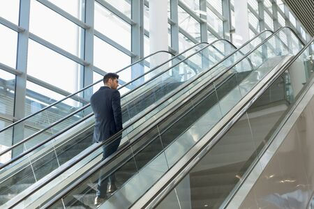 Full length rear view of young Caucasian businessman going up an escalator in a modern office building. Modern corporate start up new business concept with entrepreneur working hard Фото со стока