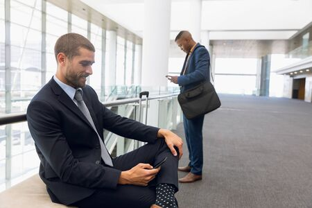 Close up side view of a young Caucasian businessman with a suitcase sitting on a bench using his smartphone in a modern corridor while a young African American businessman stands looking at his phone in the background. Modern corporate start up new business concept with entrepreneur working hard