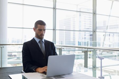 Front view of young Caucasian businessman sitting at desk using laptop computer in front of window in a modern office. Modern corporate start up new business concept with entrepreneur working hard