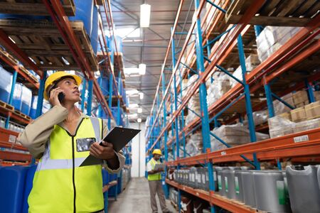 Front view of female worker looking up while talking on mobile phone in warehouse. This is a freight transportation and distribution warehouse. Industrial and industrial workers concept