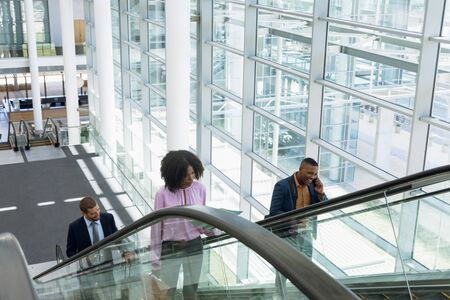 Front view of a young African American businesswoman going up an escalator in a modern building, Beside her a young African American businessman using a smartphone is going up on the next escalator. In the background a young Caucasian businessman is also coming up the escalor behind them. Modern corporate start up new business concept with entrepreneur working hard