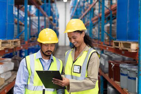Vista frontal del trabajador masculino y femenino discutiendo sobre el portapapeles en el almacén. Se trata de un almacén de transporte y distribución de mercancías. Concepto de trabajadores industriales e industriales