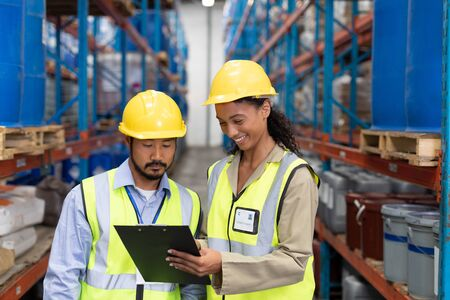 Vooraanzicht van mannelijke en vrouwelijke werknemer bespreken op klembord in magazijn. Dit is een vrachttransport- en distributiemagazijn. Industrieel en industrieel arbeidersconcept