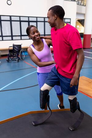 Front view of Happy African-american physiotherapist helping disabled African-american man walk with prosthetic leg on ramp in sports center. Sports Rehab Centre with physiotherapists and patients working together towards healing