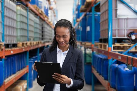 Happy female manager writing on clipboard while talking on headset in warehouse. This is a freight transportation and distribution warehouse. Industrial and industrial workers concept Banco de Imagens