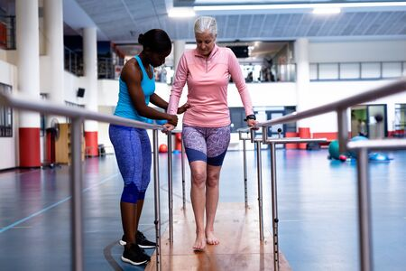 Front view of African-american female physiotherapist helping disabled Caucasian senior woman walk with parallel bars in sports center. Sports Rehab Centre with physiotherapists and patients working together towards healing Imagens