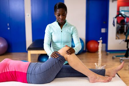 Front view of female physiotherapist giving leg massage to active senior woman in sports center. Sports Rehab Centre with physiotherapists and patients working together towards healing Imagens