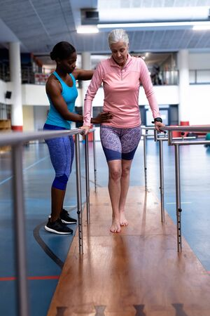 Front view of African-american female physiotherapist helping disabled Caucasian senior woman walk with parallel bars in sports center. Sports Rehab Centre with physiotherapists and patients working together towards healing