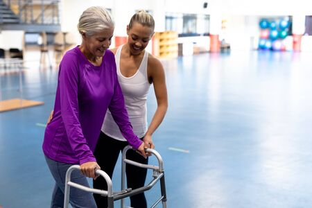 Side view of female physiotherapist helping disabled senior woman walk with walker in sports center. Sports Rehab Centre with physiotherapists and patients working together towards healing