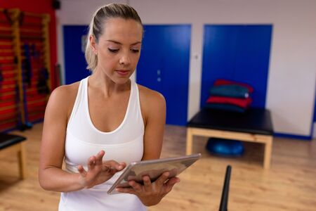 Front view of beautiful woman using digital tablet in a modern sports center. Sports Rehab Centre with physiotherapists and patients working together towards healing