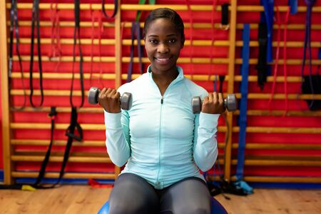 Happy woman looking at camera while exercising with dumbbell in sports center. Sports Rehab Centre with physiotherapists and patients working together towards healing