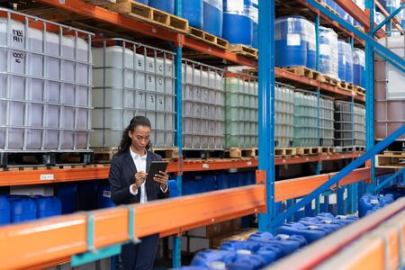 African American female manager using digital tablet in warehouse. This is a freight transportation and distribution warehouse. Industrial and industrial workers concept