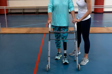 Low section of female physiotherapist helping disabled senior woman walk with walker in sports center. Sports Rehab Centre with physiotherapists and patients working together towards healing Imagens
