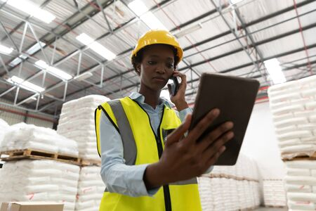 Low angle view of female worker using digital tablet while talking on mobile phone in warehouse. This is a freight transportation and distribution warehouse. Industrial and industrial workers concept Banco de Imagens