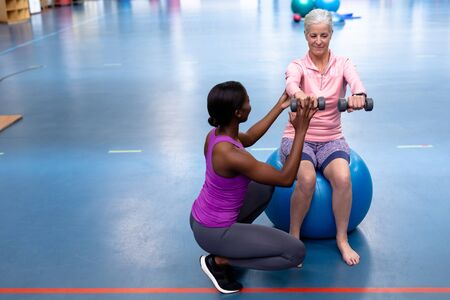 Front view of African-american Female trainer assisting disabled Caucasian senior woman to exercise with dumbbell in sports center. Sports Rehab Centre with physiotherapists and patients working together towards healing Archivio Fotografico