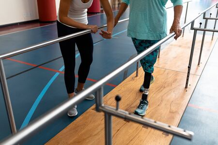 Low section of female physiotherapist helping disabled senior woman walk with parallel bars in sports center. Sports Rehab Centre with physiotherapists and patients working together towards healing