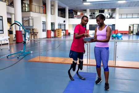 Front view of African-american female trainer and disabled African-american man discussing over digital tablet in sports center. Sports Rehab Centre with physiotherapists and patients working together towards healing