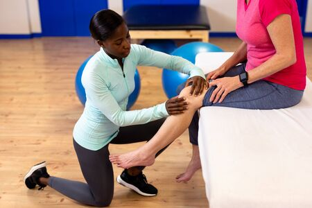 Side view of female physiotherapist giving leg massage to active senior woman in sports center. Sports Rehab Centre with physiotherapists and patients working together towards healing