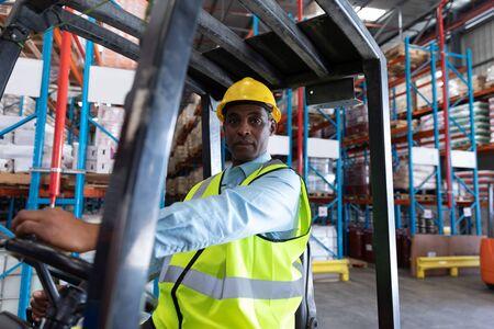 Vooraanzicht van mannelijke werknemer die naar de camera kijkt tijdens het rijden met een vorkheftruck in het magazijn. Dit is een vrachttransport- en distributiemagazijn. Industrieel en industrieel arbeidersconcept