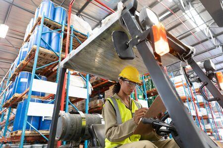Niedrige Winkelsicht auf weibliches Personal, das in die Zwischenablage schreibt, während sie auf einem Gabelstapler im Lager sitzt. Dies ist ein Gütertransport- und Distributionslager. Industrie- und Industriearbeiterkonzept