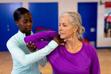 Zbliżenie: żeński fizjoterapeuta daje masaż ramion aktywnej starszej kobiety w centrum sportowym. Centrum Rehabilitacji Sportowej z fizjoterapeutami i pacjentami współpracującymi na rzecz uzdrowienia