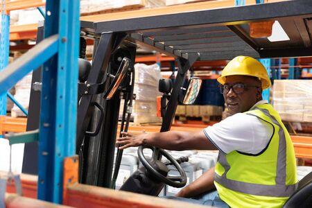 Porträt des männlichen Personals, das Gabelstapler im Lager fährt. Dies ist ein Gütertransport- und Distributionslager. Industrie- und Industriearbeiterkonzept Standard-Bild