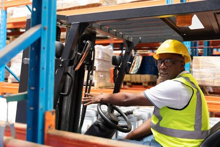 Portrait of male staff driving forklift in warehouse. This is a freight transportation and distribution warehouse. Industrial and industrial workers concept Фото со стока